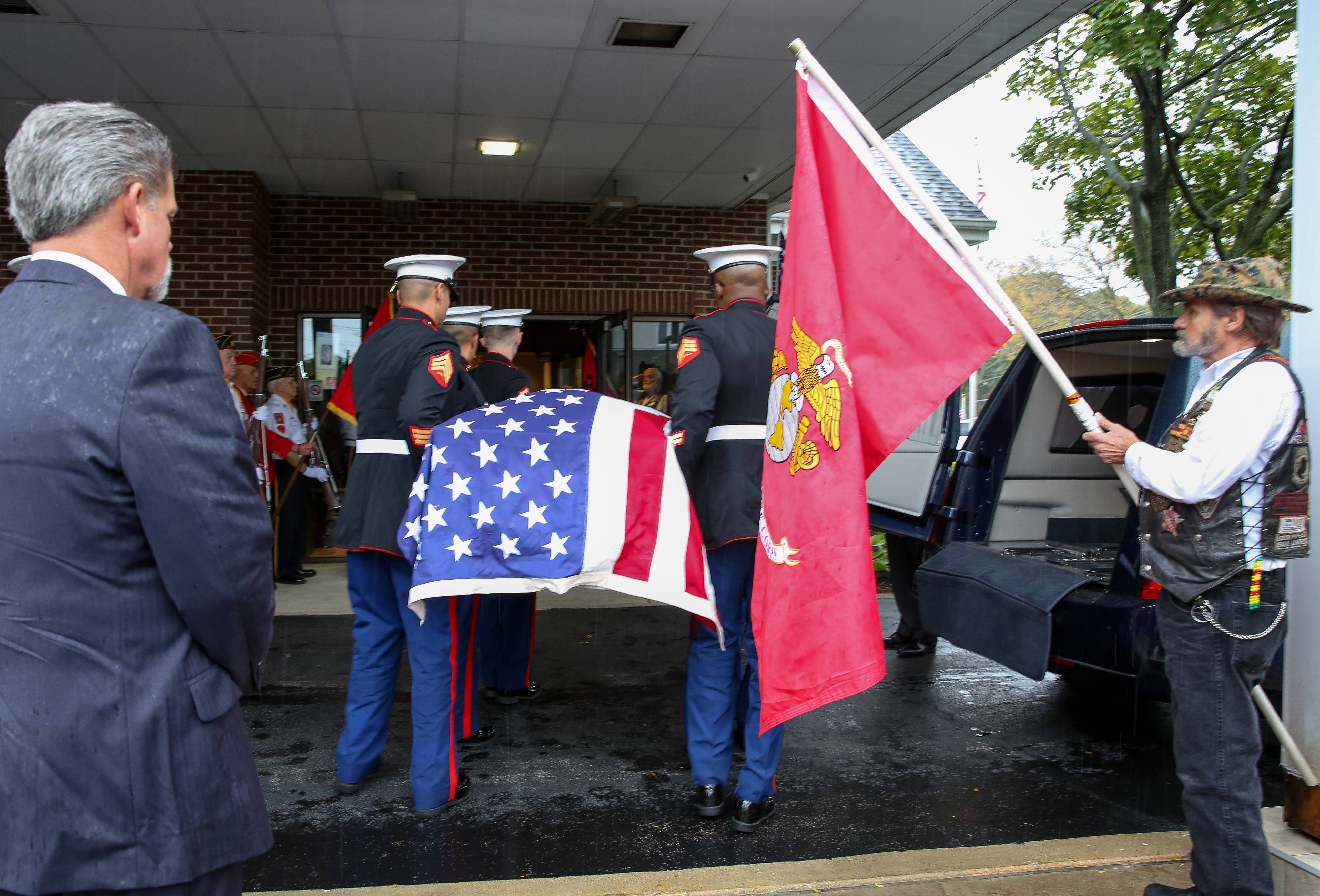 The remains of Harry Carlsen, a Marine killed in action on Nov. 20, 1943, during World War II, arrives Wednesday at Glueckert Funeral Home in Arlington Heights.