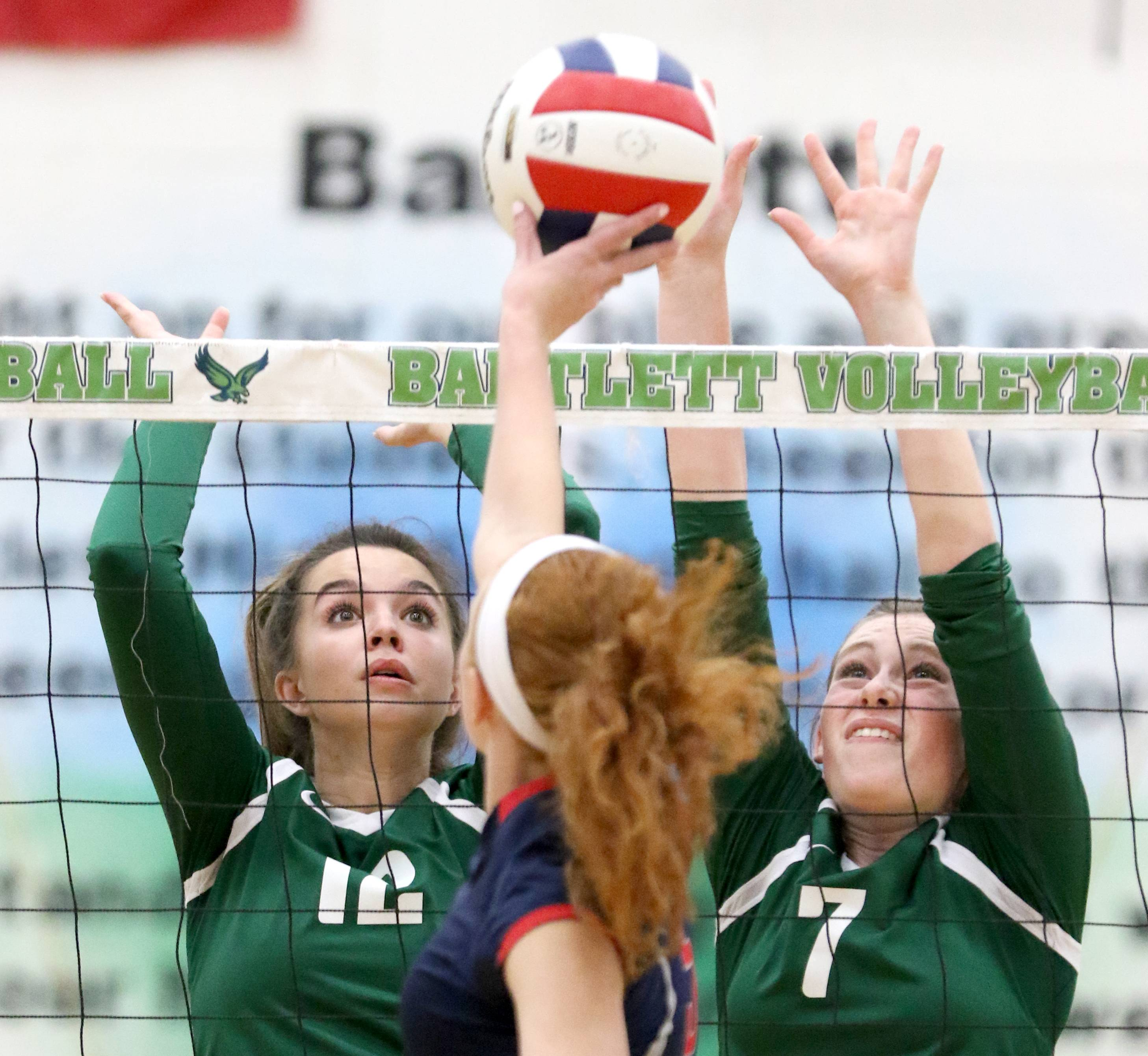 South Elgin's Hayley Fisher, center, hits the ball over the net as Bartlett's Anna Monson, left, and Emily Baggot block during the Storm's win at Bartlett on Wednesday evening.