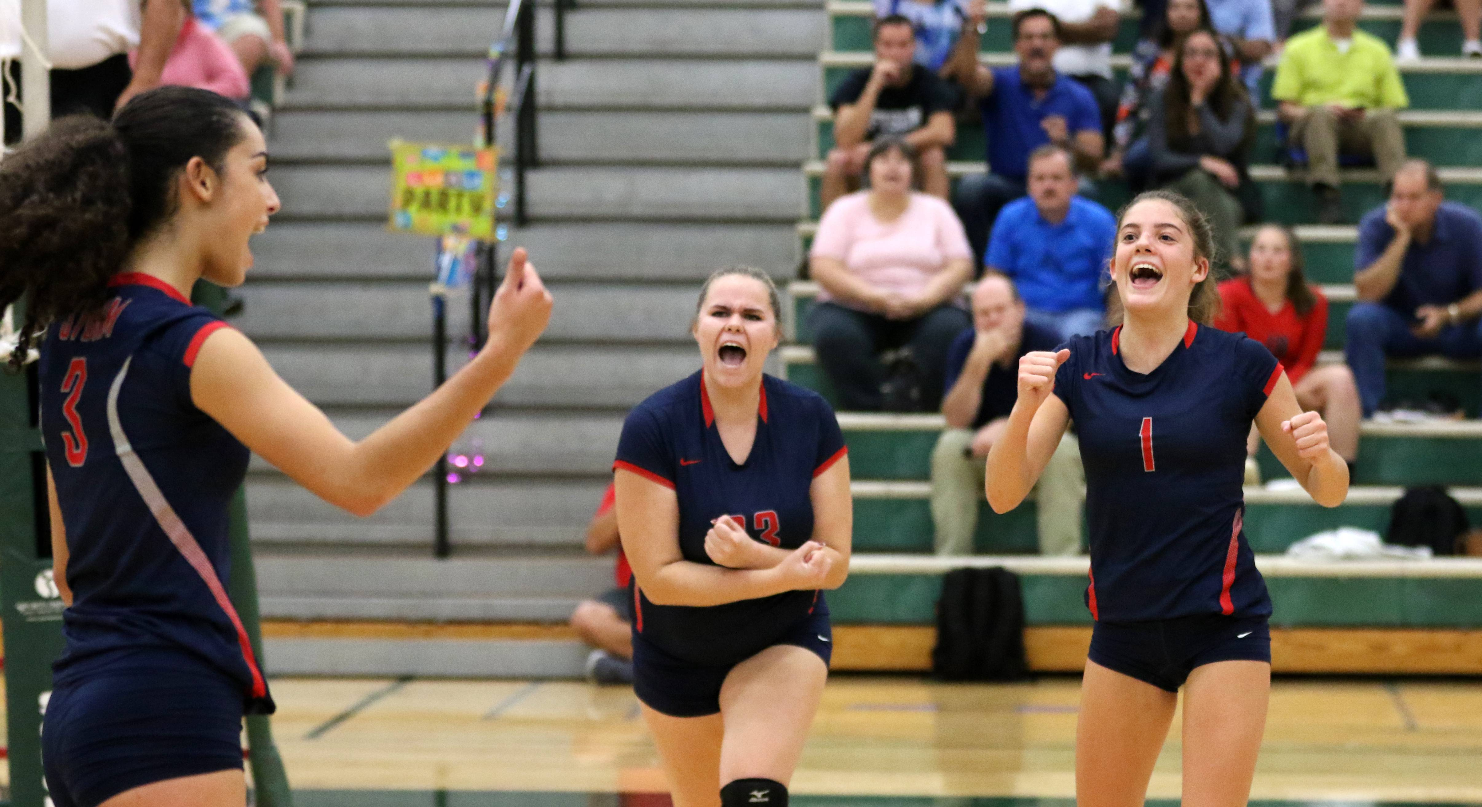 South Elgin players, from left, Angeline Negron, Kylee Hunter, and Kendall Richardson celebrate a point during varsity girls volleyball at Bartlett on Wednesday evening.