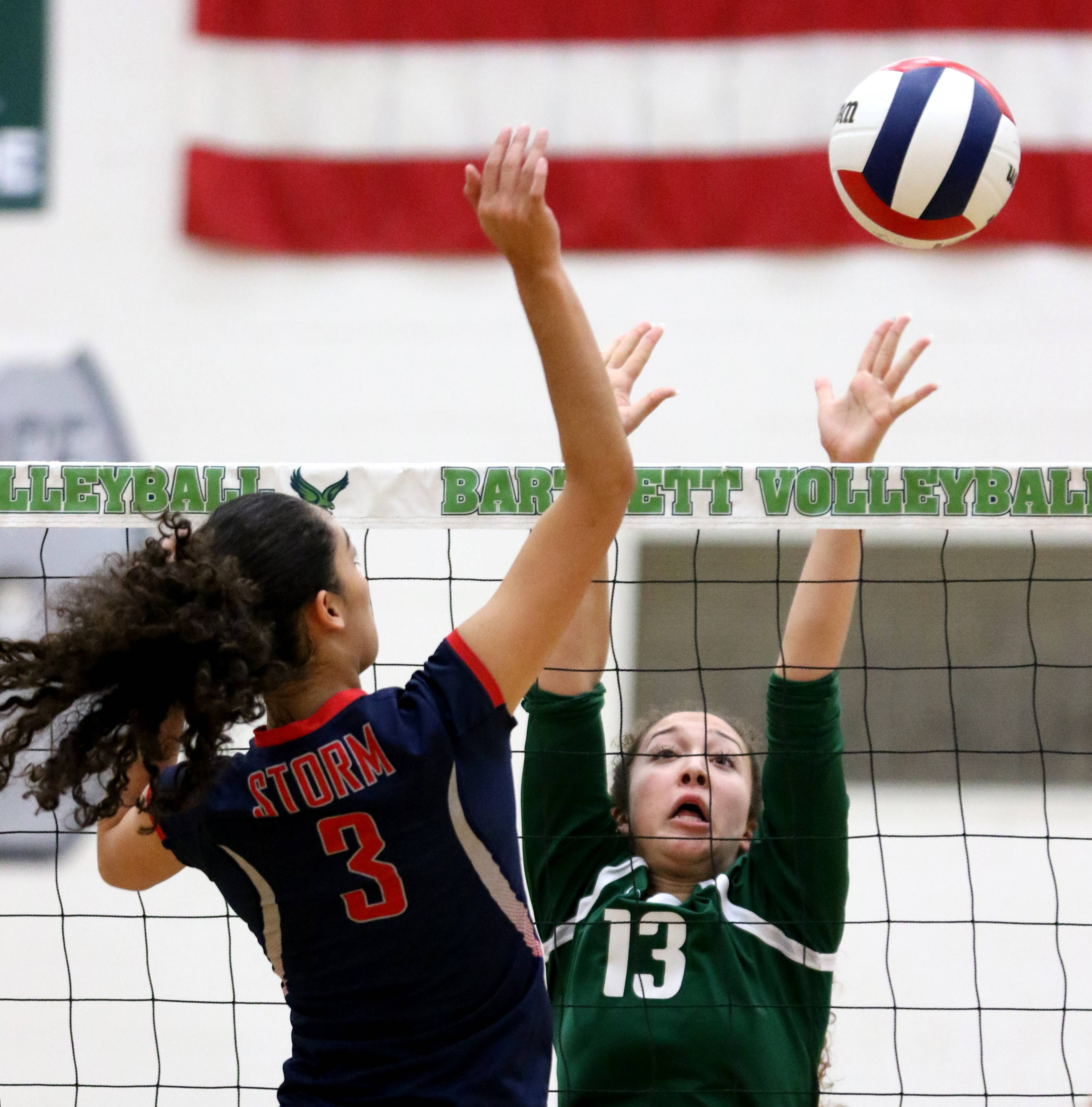 South Elgin's Angelina Negron, left, hits the ball as Bartlett's Isabella Diaz blocks during varsity girls volleyball at Bartlett on Wednesday evening.