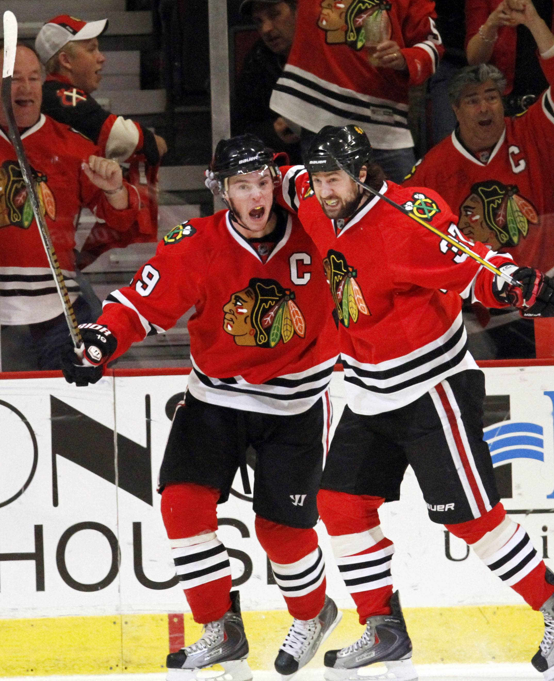 Jonathan Toews, left, celebrates with Adam Burish after scoring his goal against the Vancouver Canucks during the third period of Game 5 of the 2010 Western Conference second-round playoff series at the United Center.
