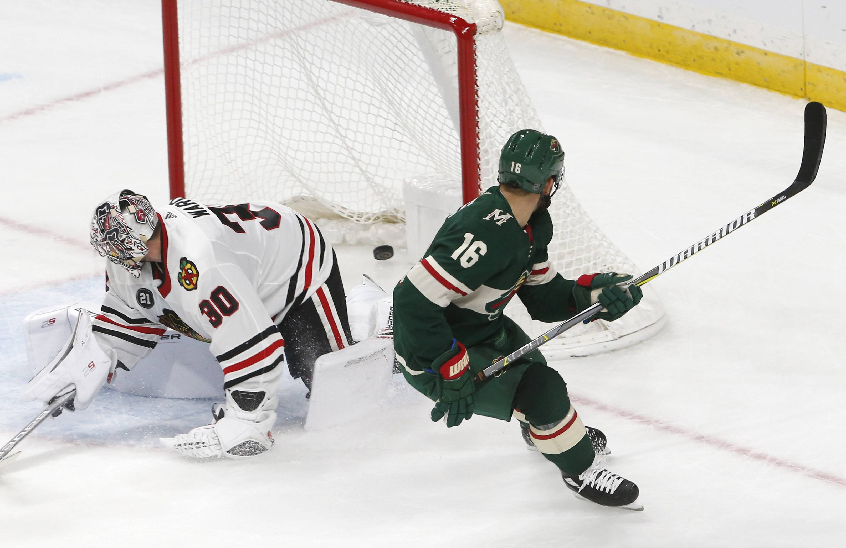 Minnesota Wild's Jason Zucker, right, watches his overtime goal against Chicago Blackhawks goalie Cam Ward in an NHL hockey game Thursday in St. Paul, Minn. The Wild won 4-3. It was Zucker's second goal of the game.