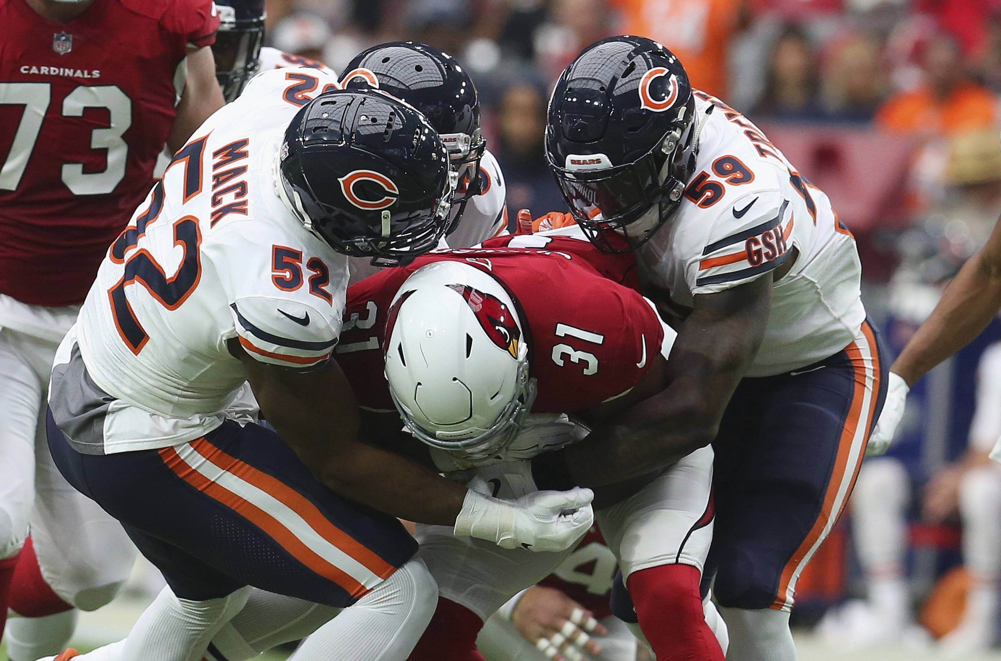 Chicago Bears linebacker Khalil Mack (52) makes a tackle on Arizona Cardinals running back David Johnson (31) with help from Danny Trevathan (59) during the first half of an NFL football game, Sunday, Sept. 23, 2018, in Glendale, Ariz.