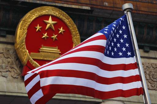 "FILE - In this Nov. 9, 2017, file photo, an American flag is flown next to the Chinese national emblem during a welcome ceremony for visiting U.S. China says accusations against an alleged spy of attempting to steal trade secrets from several American aviation and aerospace companies were ""made out of thin air."""