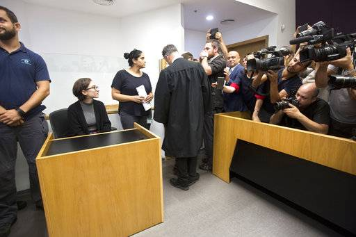 American Lara Alqasem, left, sits in a courtroom prior to a hearing at the district court in Tel Aviv, Israel, Thursday, Oct. 11, 2018. A senior Israeli cabinet minister on Wednesday defended the government's handling of the case of an American graduate student held in detention at the country's international airport for the past week over allegations that she promotes a boycott against the Jewish state.