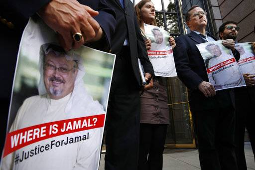 Alyssa Edling, center, and Thomas Malia, second from right, both with PEN America, join others as they hold signs of missing journalist Jamal Khashoggi, during a news conference about his disappearance in Saudi Arabia, Wednesday, Oct. 10, 2018, in front of The Washington Post in Washington.