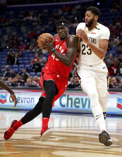 Toronto Raptors forward Pascal Siakam (43) drives against New Orleans Pelicans forward Anthony Davis (23) during the first half of a preseason NBA basketball game in New Orleans, Thursday, Oct. 11, 2018.