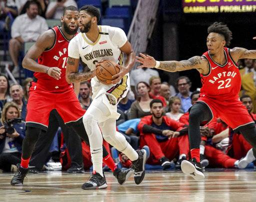 Toronto Raptors guard Malachi Richardson (22) reaches for the ball held by New Orleans Pelicans forward Anthony Davis (23) as Davis is guarded by Toronto Raptors center Greg Monroe (15) in the first half of a preseason NBA basketball game in New Orleans, Thursday, Oct. 11, 2018.