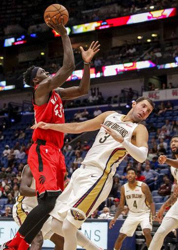 New Orleans Pelicans forward Nikola Mirotic (3) is called for blocking on a shot by Toronto Raptors forward Pascal Siakam (43) during the first half of a preseason NBA basketball game in New Orleans, Thursday, Oct. 11, 2018.