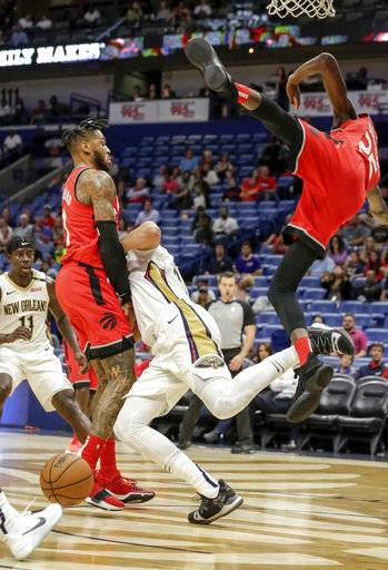 New Orleans Pelicans forward Anthony Davis (23) collides with Toronto Raptors forward Chris Boucher (25) and center Eric Moreland (1) during the second half of a preseason NBA basketball game in New Orleans, Thursday, Oct. 11, 2018. Davis and Boucher left the game after the play. The Raptors won 134-119.