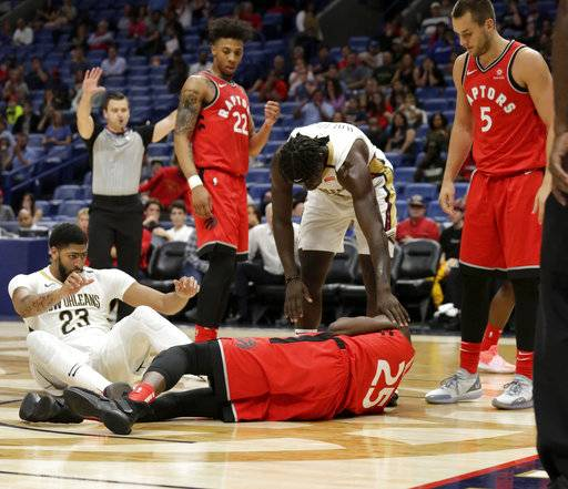 Toronto Raptors forward Chris Boucher (25) and New Orleans Pelicans forward Anthony Davis (23) hit the floor after Davis collided with Boucher and Toronto Raptors center Eric Moreland (1) during the second half of a preseason NBA basketball game in New Orleans, Thursday, Oct. 11, 2018. Davis and Boucher left the game after the play. The Raptors won 134-119.