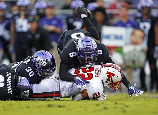 Texas Tech's Seth Collins (22) is tackled by TCU's Innis Gaines (6) during the first half of an NCAA college football game Thursday, Oct. 11, 2018, in Fort Worth, Texas. (Brad Tollefson/Lubbock Avalanche-Journal via AP)