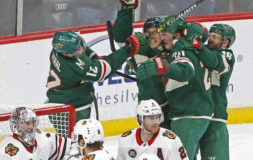 Minnesota Wild's Ryan Suter, second from right, is mobbed by teammates after scoring against Chicago Blackhawks goalie Cam Ward, lower left, to tie the score during the third period of an NHL hockey game Thursday, Oct. 11, 2018, in St. Paul, Minn. The Wild won 4-3 in overtime.