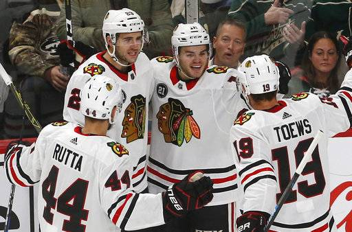 Chicago Blackhawks' Alex DeBrincat, second from right, is congratulated by teammates after scoring against Minnesota Wild goalie Devan Dubnyk during the first period of an NHL hockey game Thursday, Oct. 11, 2018, in St. Paul, Minn.
