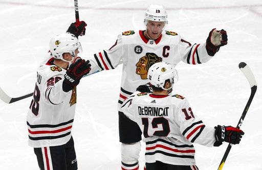 Chicago Blackhawks' Henri Jokiharju, left, and Jonathan Toews, top, congratulate Alex DeBrincat on a power-play goal against Minnesota Wild goalie Devan Dubnyk during the third period of an NHL hockey game Thursday, Oct. 11, 2018, in St. Paul, Minn. It was DeBrincat's second goal of the game. The Wild won 4-3 in overtime.