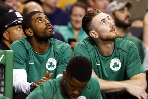 FILE - In this Oct. 9, 2017 file photo Boston Celtics' Kyrie Irving, left, and Gordon Hayward look on from the bench during the first quarter of a preseason NBA basketball game against the Philadelphia 76ers in Boston. Last season hopes were high for the Celtics in the preseason with a new-look roster that included Irving and Hayward. Five minutes into the season opener everything changed with Hayward's gruesome leg injury. It happened again late in the season with Irving was lost to knee surgery. With both back and healthy, Boston is embracing being called the presumptive favorites in the Eastern Conference.