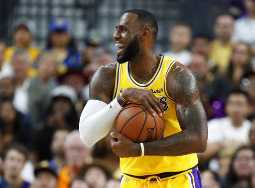 Los Angeles Lakers forward LeBron James reacts after a play against the Golden State Warriors during the first half of an NBA preseason basketball game Wednesday, Oct. 10, 2018, in Las Vegas.