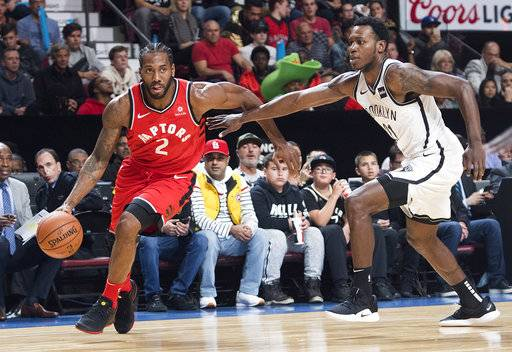 Toronto Raptors' Kawhi Leonard (2) drives to the basket as Brooklyn Nets' Treveon Graham defends during the first half of an NBA basketball preseason game Wednesday, Oct, 10, 2018, in Montreal. (Graham Hughes/The Canadian Press via AP)