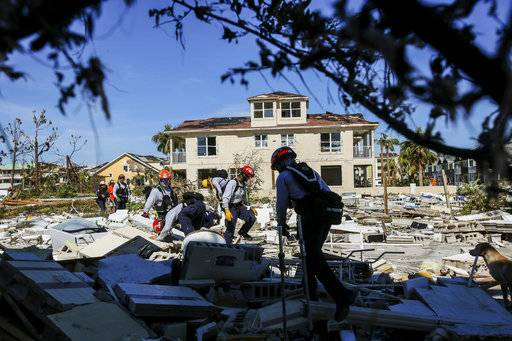 Members from South Florida Task Force search a flattened home destroyed by Hurricane Michael in Mexico Beach, Fla., Friday, Oct. 12, 2018, after Hurricane Michael went through the area on Wednesday. Mexico Beach, the ground-zero town, was nearly obliterated by the hurricane, an official said Friday as the scale of the storm's fury became ever clearer. (Bronte Wittpenn/Tampa Bay Times via AP)