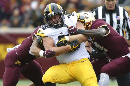 FILE - In this Saturday, Oct. 6, 2018, file photo, Iowa's Mitch Riggs is tackled by Minnesota's defensive back Terell Smith during an NCAA college football game in Minneapolis. Iowa faces Indiana on Saturday.