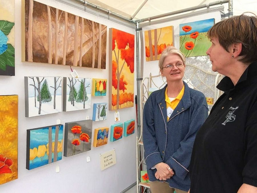 June Pryor, left, from Oxford, Mississippi, explains the inspiration for her acrylic paintings to a customer at the Mundelein Arts Festival last month.