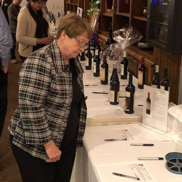 "Brigitta Kempken checks out the various wine selections at the YMCA's annual ""Wine & Craft Beer Auction"" on Friday, Nov. 2, at the Golf Club of Illinois in Algonquin."
