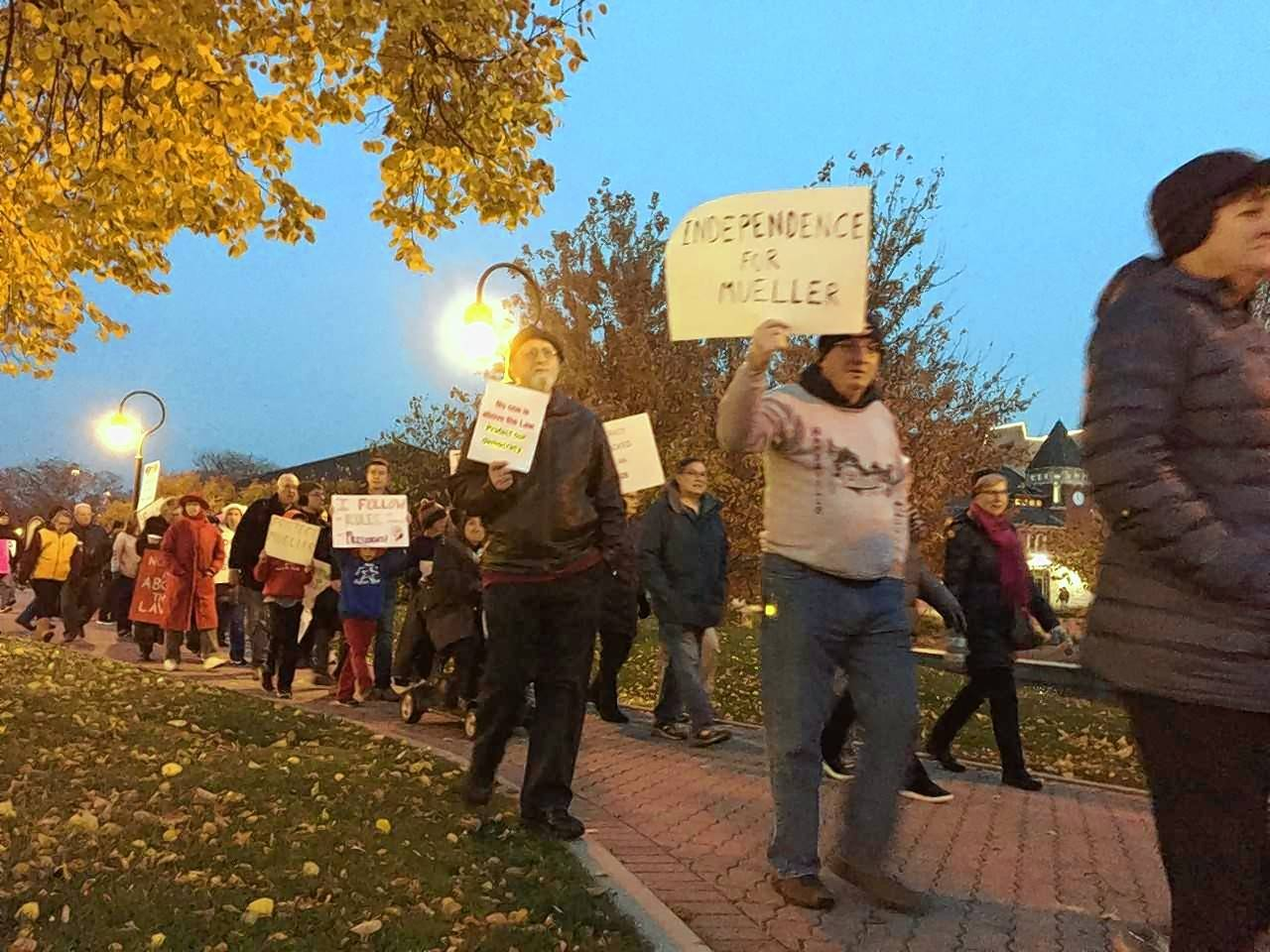 Protesters march along the Riverwalk on Thursday afternoon in downtown Naperville, showing their anger over the forced resignation of former U.S. Attorney General Jeff Sessions and expressing their fears about the consequences of Sessions' ouster for Special Counsel Robert Mueller's investigation into Russian election meddling.