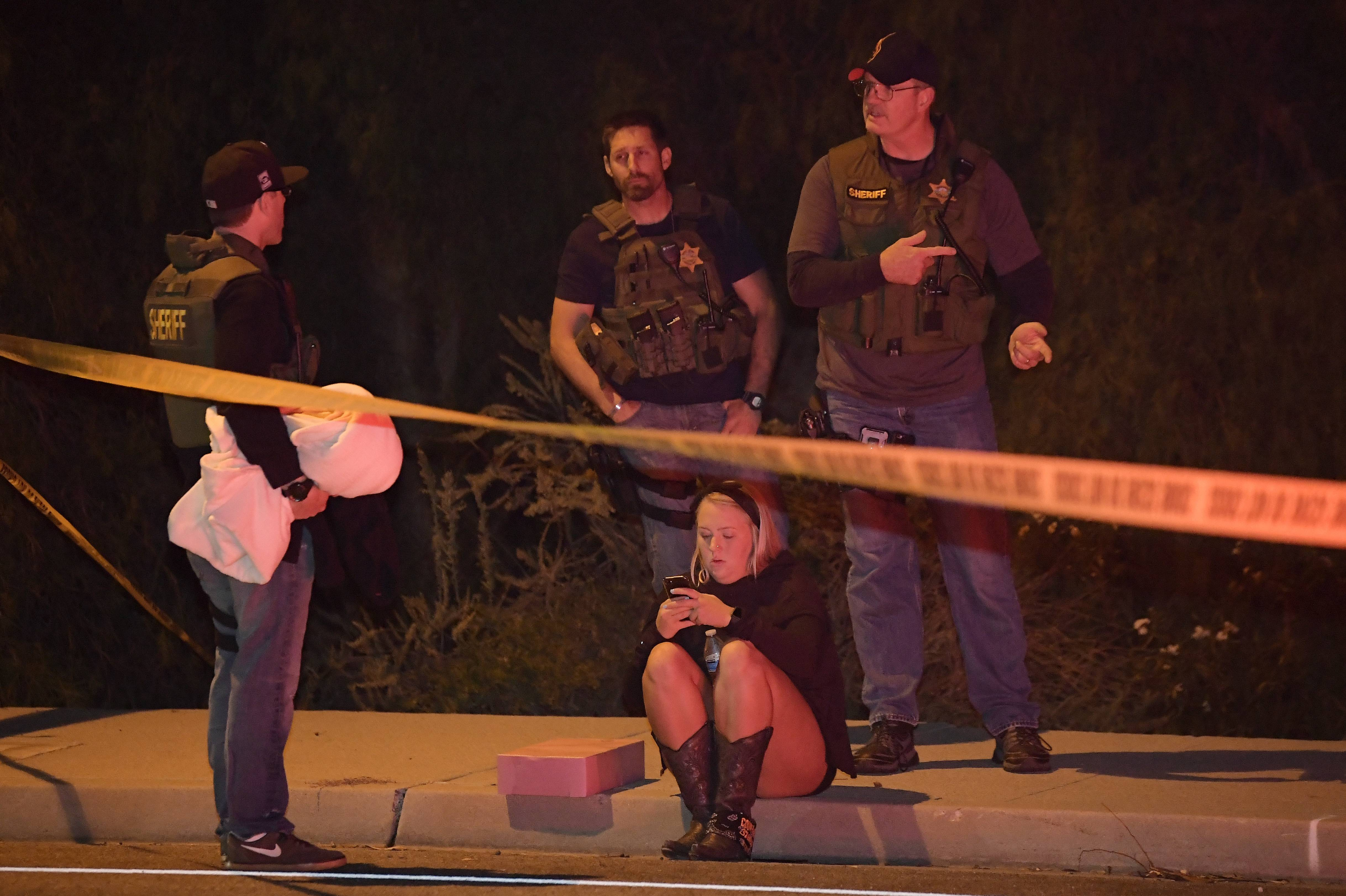 "Sheriff's deputies speak Thursday to a potential witness as they stand near the scene in Thousand Oaks, California, where a gunman opened fire Wednesday inside a country dance bar crowded with hundreds of people on ""college night,"" wounding 11 people including a deputy who rushed to the scene. Ventura County sheriff's spokesman says gunman is dead inside the bar."
