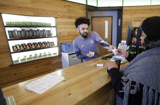 In this Wednesday, Oct. 17, 2018 photo patient service associate Nelson Rivera III, left, sells medical cannabis products to Victoria Silva, of Amherst, Mass., right, at a New England Treatment Access medical marijuana dispensary, in Northampton, Mass. Within days perhaps, the medical marijuana dispensary in Northampton expects to receive the final go-ahead to throw its doors open to anyone 21 or older who wants to purchase cannabis products ranging from flower to edibles, creams and even suppositories.