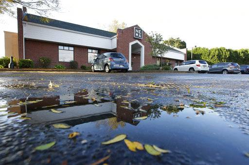 In this Wednesday, Oct. 17, 2018 photo the New England Treatment Access medical cannabis dispensary is reflected in a puddle, in Northampton, Mass. Within days perhaps, the medical marijuana dispensary in Northampton expects to receive the final go-ahead to throw its doors open to anyone 21 or older who wants to purchase cannabis products ranging from flower to edibles, creams and even suppositories.