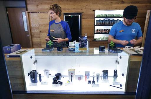 In this Wednesday, Oct. 17, 2018 photo patient service associates Savannah Stuitje, left, and Josh Hirst, right, stand at a counter that features a display of vape dispensers, below, that could be used for legal recreational cannabis, at New England Treatment Access medical marijuana dispensary, in Northampton, Mass. Within days perhaps, the medical marijuana dispensary in Northampton expects to receive the final go-ahead to throw its doors open to anyone 21 or older who wants to purchase cannabis products ranging from flower to edibles, creams and even suppositories.