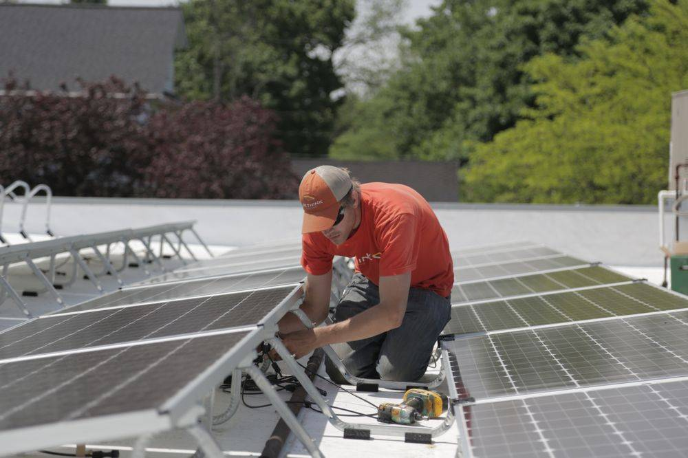 A Rethink Electric employee installs a rooftop solar energy system.