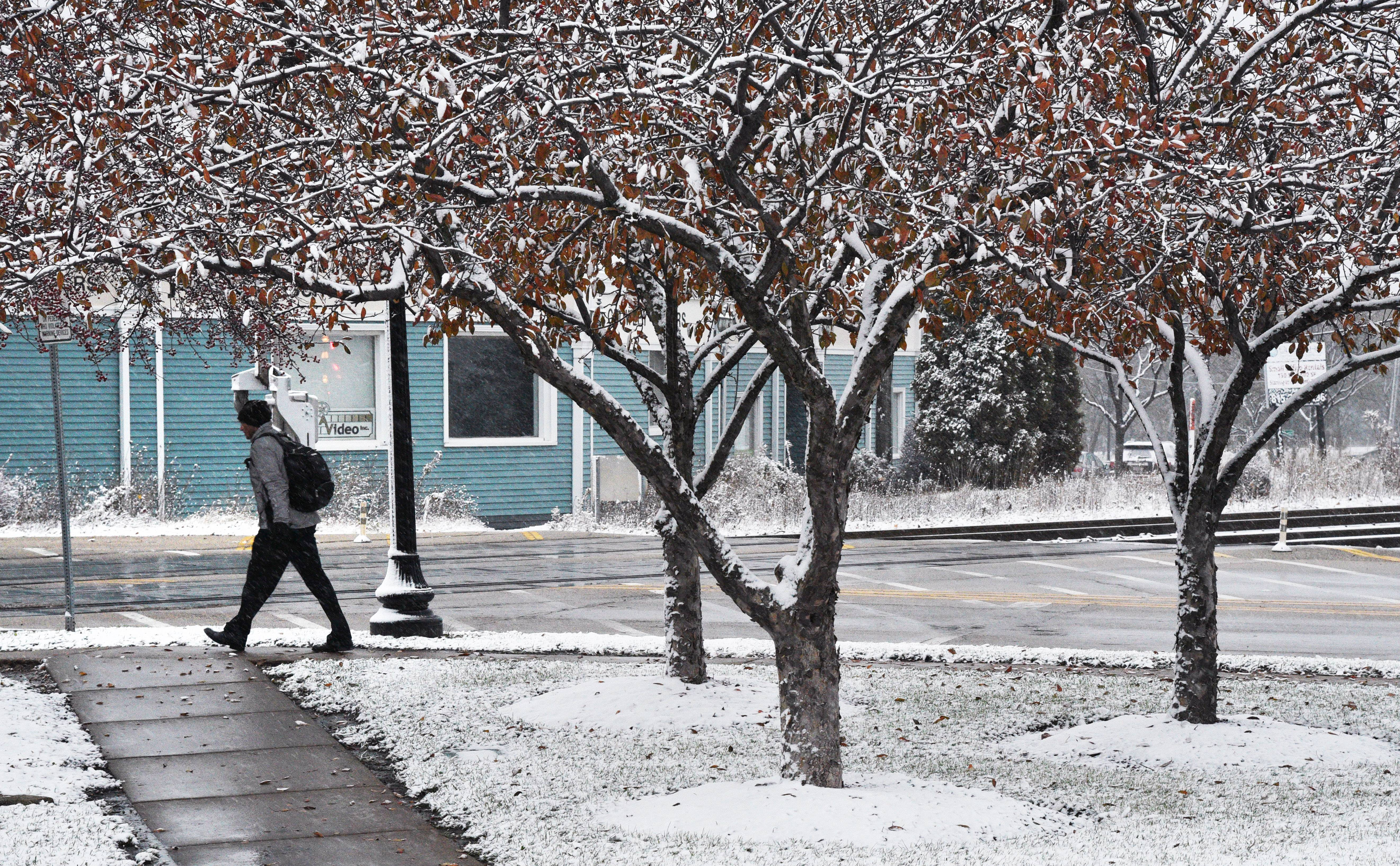A commuter heads to the Crystal Lake Metra station Friday morning as snow falls, covering grassy areas and leaves.