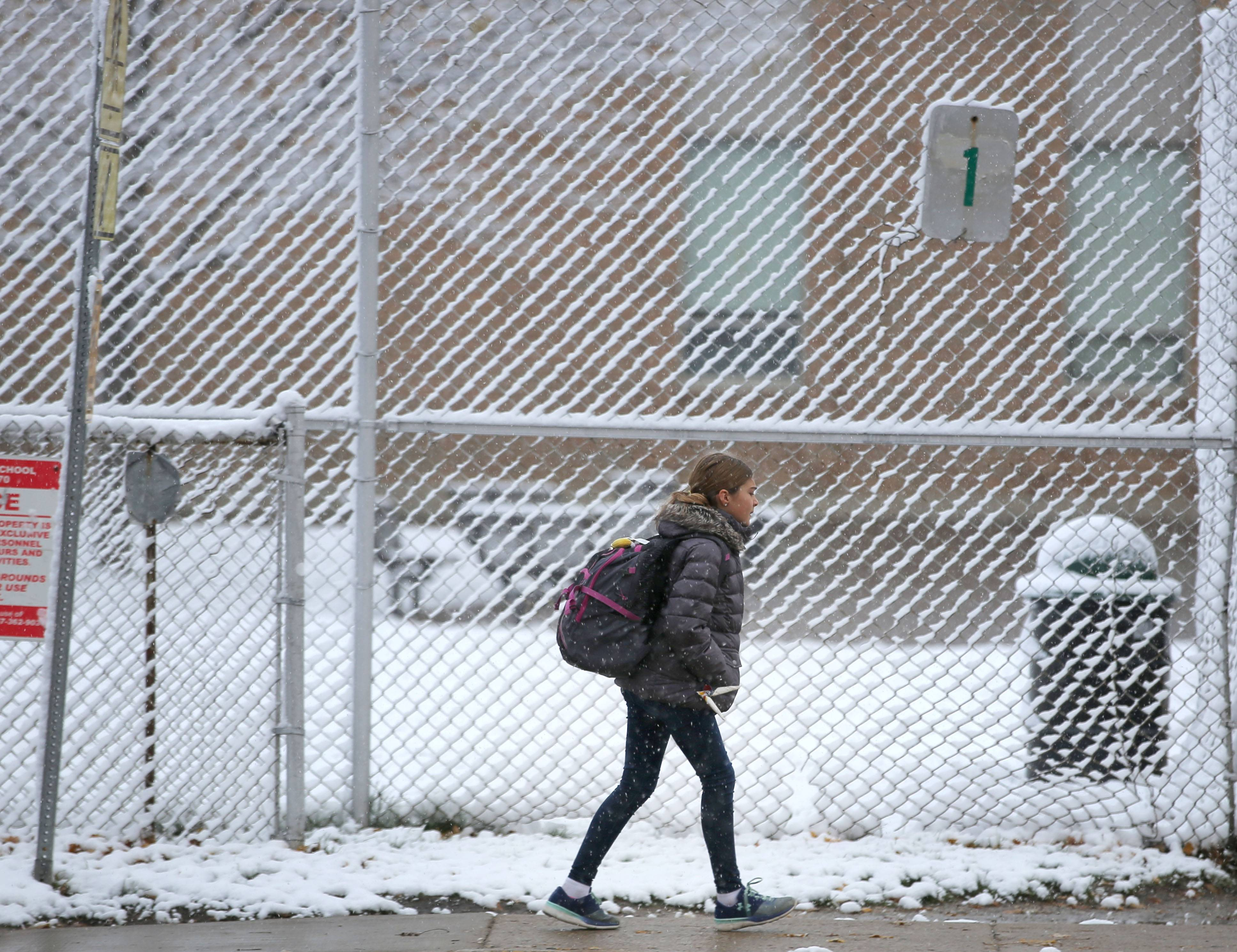 Students head to Highland Middle School in Libertyville after an overnight snow blanketed the area Friday.