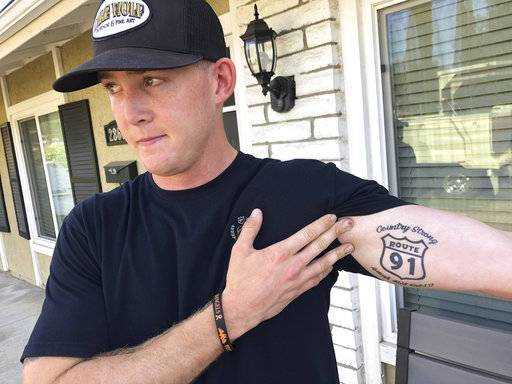 Brendan Kelly speaks with reporters outside his home, as he shows his Route 91 tattoo, Thursday, Nov. 8, 2018, in Thousand Oaks, Calif. Kelly, a Marine who was at Borderline Bar and Grill on Wednesday night, helped people get out after a gunman opened fire at the establishment. Kelly also survived the Las Vegas Route 91 Harvest Festival shooting in 2017.