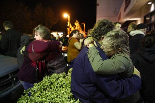Eva Mills, right, and Holden Grzywacz, two survivors of the Las Vegas mass shooting, mourn the death of Sean Adler during a vigil at the Rivalry Roasters coffee shop Thursday, Nov. 8, 2018, in Simi Valley, Calif. Adler was killed in Wednesday night's shooting at the Borderline Bar and Grill in Thousand Oaks, Calif.