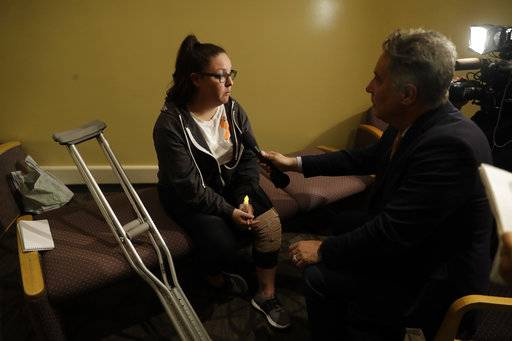 Dani Merrill, left, who survived both the Las Vegas concert shooting and the Thousand Oaks bar shooting conducts an interview during a vigil to remember victims of a mass shooting Thursday, Nov. 8, 2018, in Thousand Oaks, Calif. Terrified patrons hurled barstools through windows to escape or threw their bodies protectively on top of friends as a Marine combat veteran killed multiple people at a country music bar in an attack that added Thousand Oaks to the tragic roster of American cities traumatized by mass shootings.