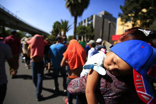 A sleeping Honduran girl is carried as a group of Central American migrants, representing the thousands participating in a caravan trying to reach the U.S. border, undertake an hours-long march to the office of the United Nations' humans rights body in Mexico City, Thursday, Nov. 8, 2018. Members of the caravan which has stopped in Mexico City demanded buses Thursday to take them to the U.S. border, saying it tis too cold and dangerous to continue walking and hitchhiking.
