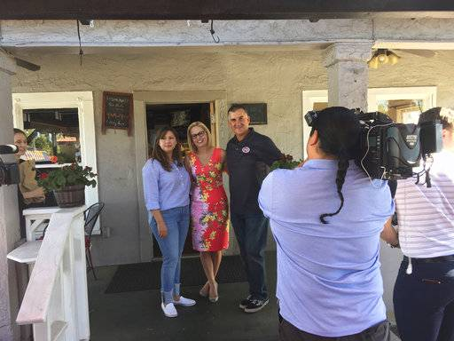 U.S. Senate candidate and Democratic Rep. Kyrsten Sinema poses in between America Corrales and Terry Bortin in front of media on Tuesday, Nov. 6, 2018, at the couple's taco restaurant in Phoenix. Sinema, who is locked in a tight race with Republican Rep. Martha McSally is spending the final hours of election day talking to voters.