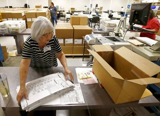 Workers at the Maricopa County Recorder's Office go through ballots Thursday, Nov. 8, 2018, in Phoenix. There are several races too close to call in Arizona, especially the Senate race between Democratic candidate Kyrsten Sinema and Republican candidate Martha McSally.