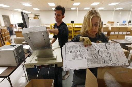 Workers organize ballots at the Maricopa County Recorder's Office Thursday, Nov. 8, 2018, in Phoenix. There are several races too close to call in Arizona, especially the Senate race between Democratic candidate Kyrsten Sinema and Republican candidate Martha McSally.