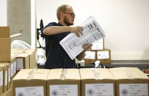 A worker carries ballots to be verified at the Maricopa County Recorder's Office Thursday, Nov. 8, 2018, in Phoenix. There are several races too close to call in Arizona, especially the Senate race between Democratic candidate Kyrsten Sinema and Republican candidate Martha McSally.