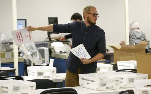 A worker prepares volunteers to verify ballots at the Maricopa County Recorder's Office Thursday, Nov. 8, 2018, in Phoenix. There are several races too close to call in Arizona, especially the Senate race between Democratic candidate Kyrsten Sinema and Republican candidate Martha McSally.