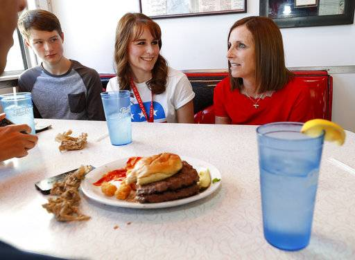 Arizona Republican senatorial candidate Martha McSally, right, speaks with Caleb Klein and his sister, Grace Klein, Tuesday, Nov. 6, 2018, at Chase's diner in Chandler, Ariz. McSally and Democratic challenger Kirsten Sinema are seeking the senate seat being vacated by Jeff Flake, R-Ariz., who is retiring in January.