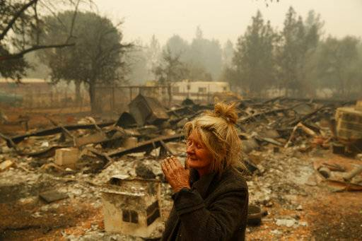 "Cathy Fallon reacts as she stands near the charred remains of her home, Friday, Nov. 9, 2018, in Paradise, Calif. ""I'll be darned if I'm going to let those horses burn in the fire,"" said Fallon, who stayed on her property to protect her 14 horses, all of which survived."