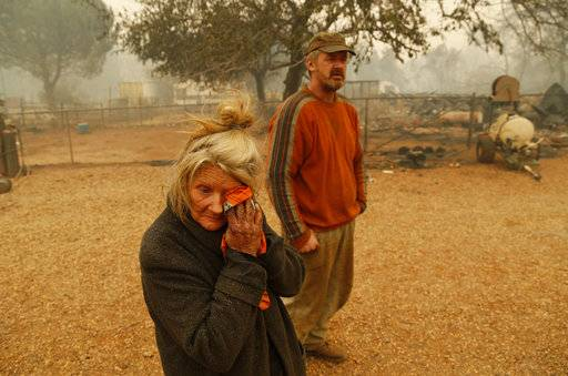 "Cathy Fallon wipes her face beside her son Gabriel Fallon as she stands near the charred remains of her home Friday, Nov. 9, 2018, in Paradise, Calif. ""I'll be darned if I'm gonna let those horses burn in the fire"" said Fallon, who stayed on her property to protect her 14 horses, ""It has to be true love."" All of the horses survived."