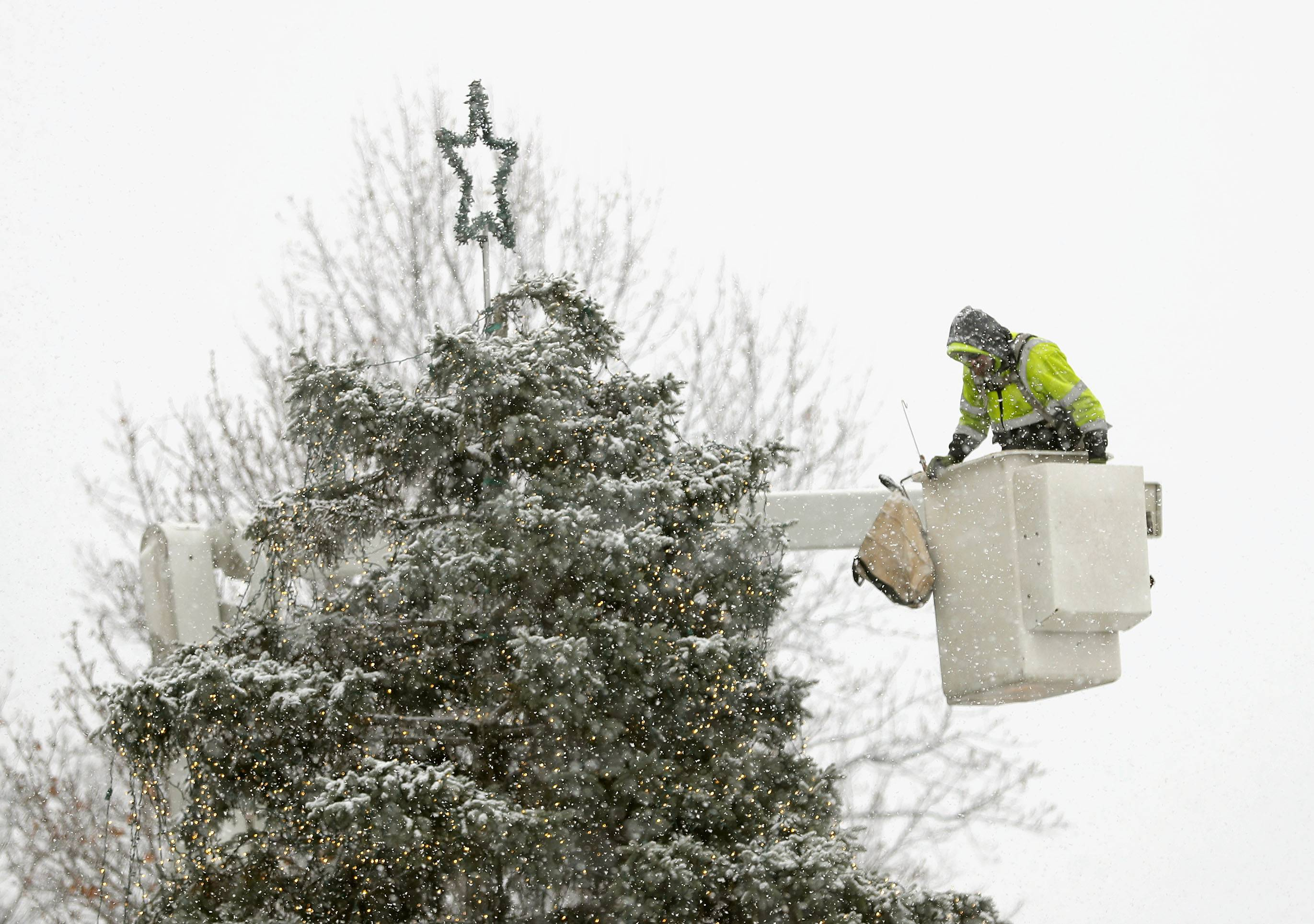 Dave Heurich of Libertyville Public Works decorates the tree in Cook Park as a winter storm pushed through the area Thursday morning.