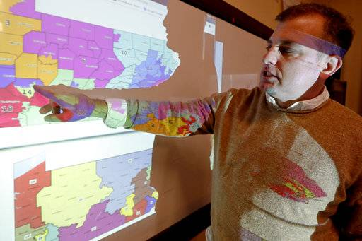 "William Marx, points to projected images of the old congressional districts of Pennsylvania on top, and the new re-drawn districts on the bottom, while standing in the classroom where he teaches civics in Pittsburgh on Friday, Nov. 16, 2018. Marx was a plaintiff in the Pennsylvania lawsuit that successfully challenged the Republican-drawn congressional maps. Marx said he believes the new district boundaries resulted in ""a more fair congressional representation of the will of the people in Pennsylvania."""