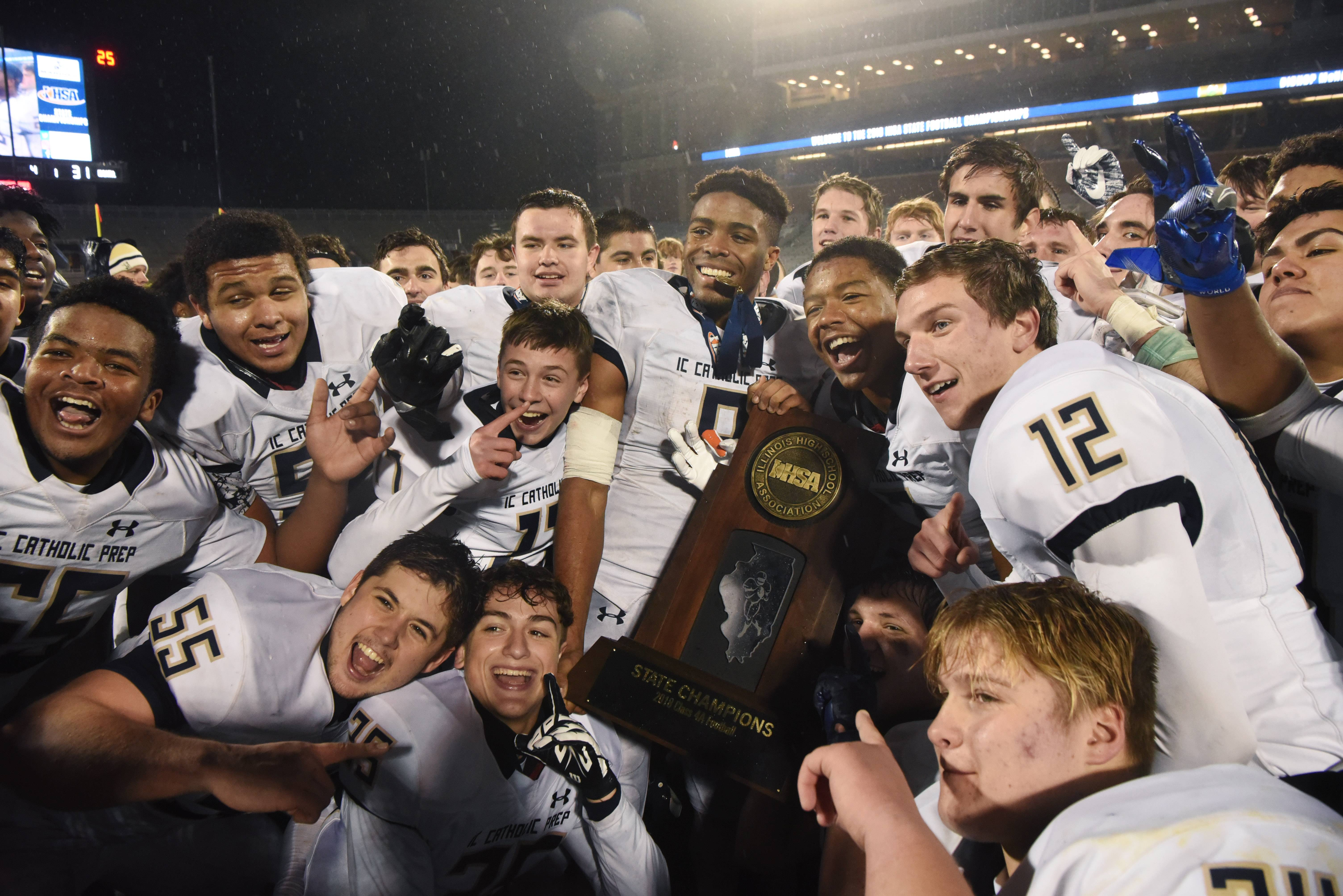 IC Catholic players celebrate with their trophy following the Class 4A state football championship at Memorial Stadium in Champaign Friday. IC Catholic defeated Bishop McNamara 31-21.