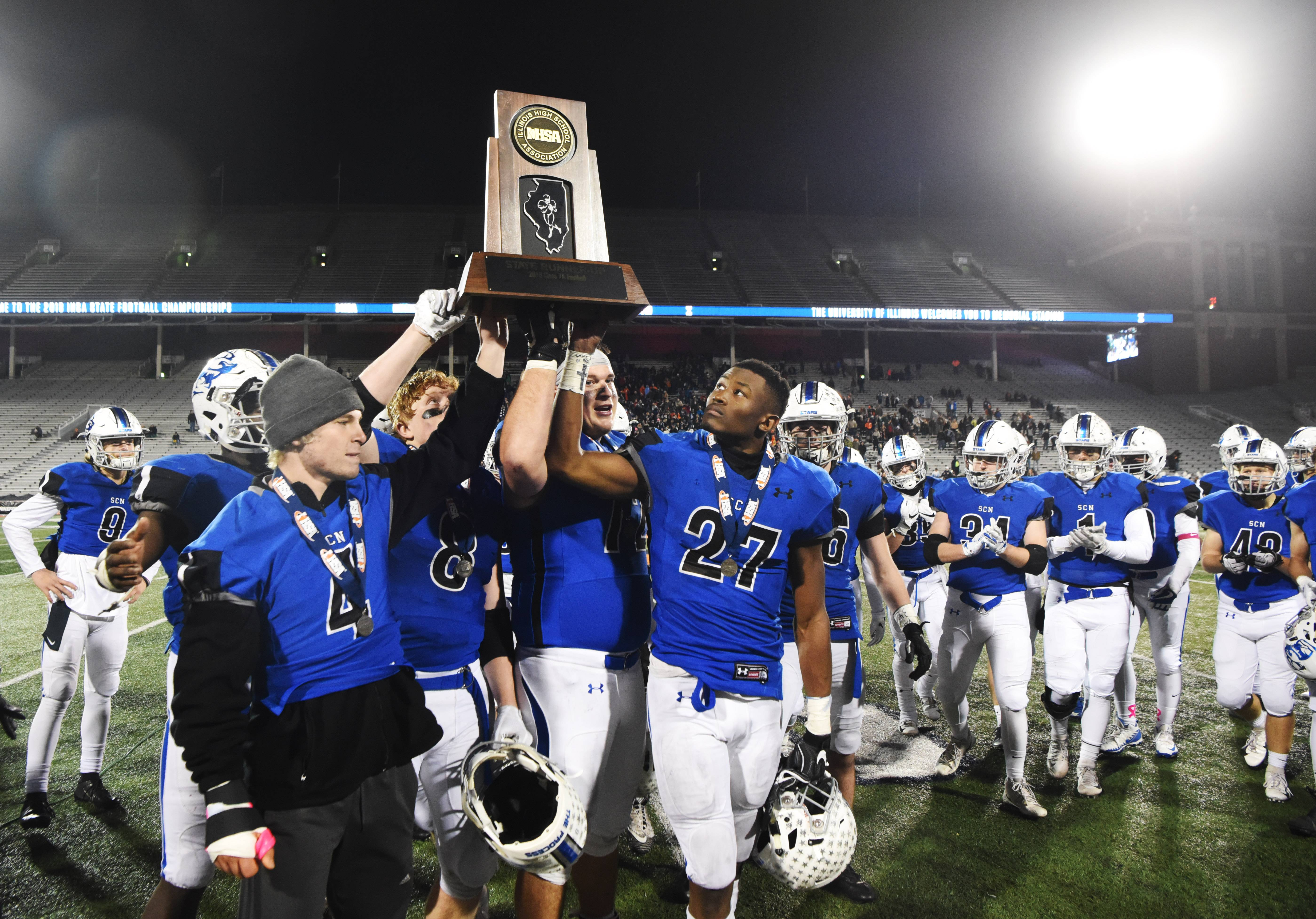 St. Charles North captains Daniel Daley (4), Ben Furtney (8), Alex Westendorf (72) and Tyler Nubin (27) hold the second-place trophy following their loss to Nazareth during the Class 7A state football championship at Memorial Stadium in Champaign Saturday.